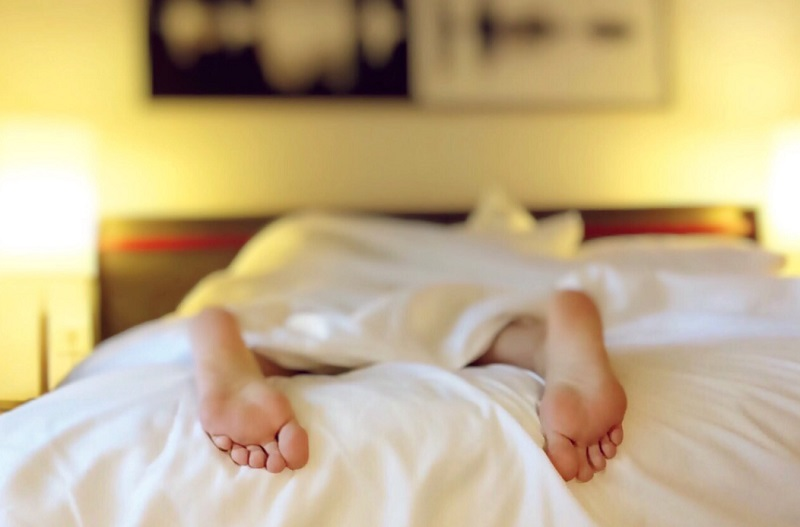 Person in bed with feet poking out under the sheets - Feel More Alert
