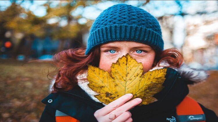 Redheaded girl wearing knitted cap , holding a fall leaf - How to prevent bullying