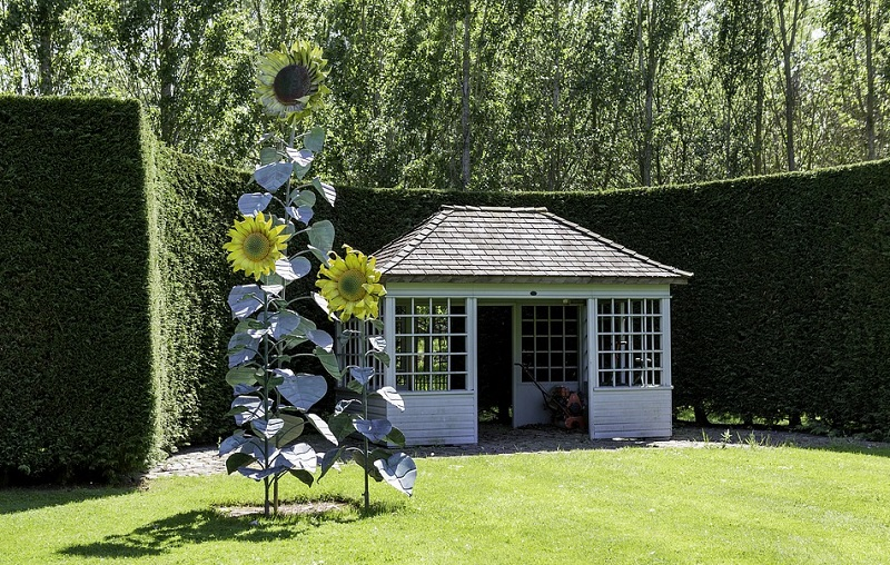 """""""Summer House"""" on well manicured lawn with high hedge and large sunflower sculpture - Garden Upgrades"""