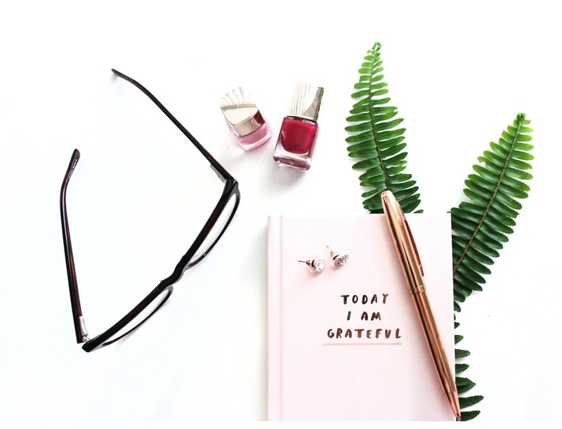 Flat Lay of glasses nail polish, journal , pen and ferns - Custom-Made Diamond Jewellery