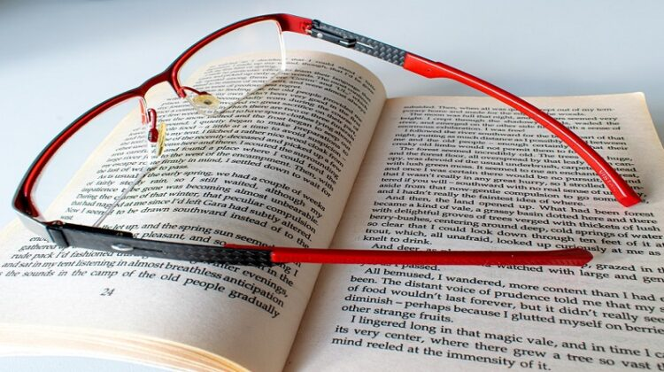 Red and black Glasses sitting on top of an open book - reading benefits for your health and well being
