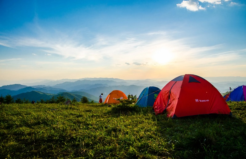 Tents on a grassy spot over looking misty mountains - vacation or staycation