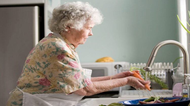 Elderly woman in floral dress and apron washing vegetables in kitchen sink - Aging in Place