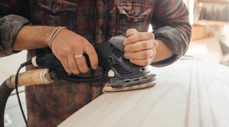Man sanding wood with orbital sander - Benefits of having an orbital sander