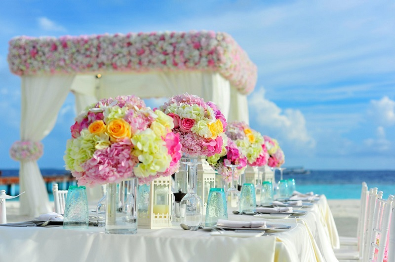 Bright Wedding Reception Table on Beach with Pinks, Yellow, and Orange Flowers - Finding the Best Flower Supplier in Your Area