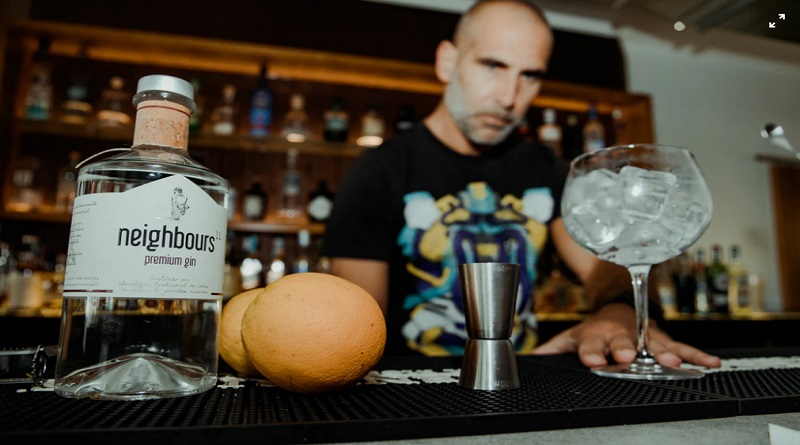 Bartender behind bar with bottle of gin , oranges, and glass with ice - Gin Bar Ideas that Will Help Your Customers Get the Best Drinking Experience
