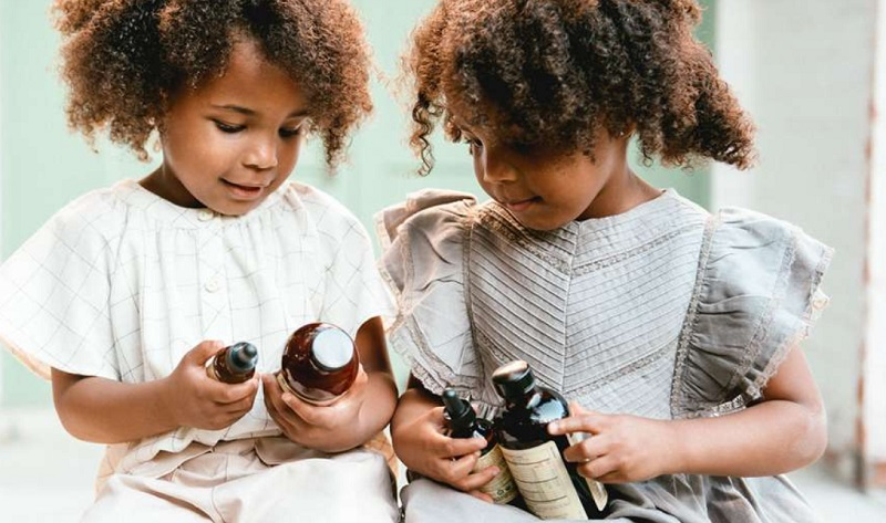 Adorable Little Girls holding bottles of vitamins from ChildLife Essentials