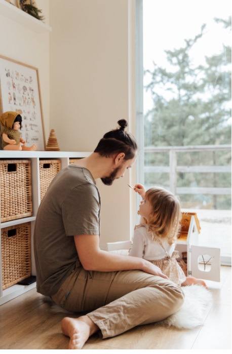 Father and young daughter sitting on floor in front of large window - 4 Ways to help your Child feel Valued