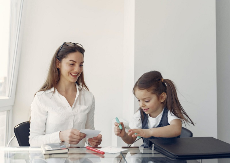 Mother and small daughter working at desk together - 4 Ways to help your Child feel Valued
