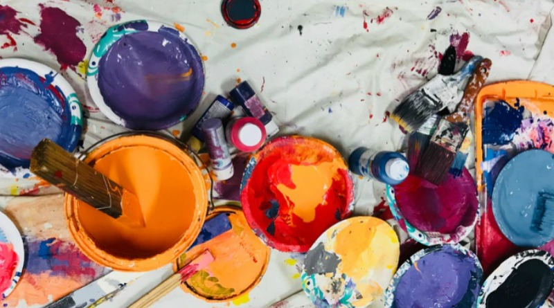 Open cans of paint and paint brushes on drop cloth - Choose the Right Paint