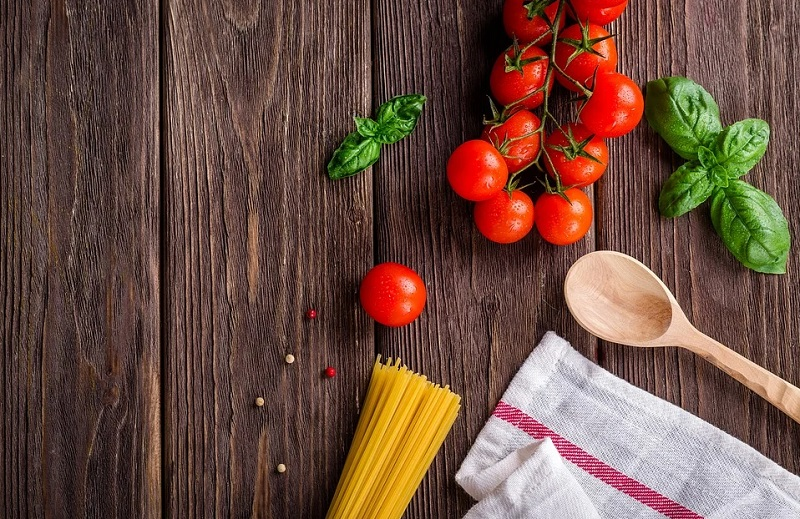 Spaghetti, cherry tomatoes, fresh herbs, a wooden spoon and dish towel, on wooden table - Updating Your Kitchen