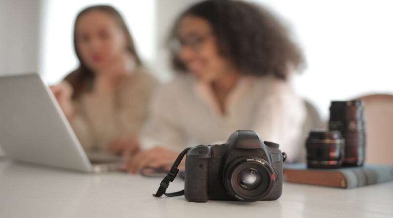 Two working on a laptop with camera, and lenses on desk - Best practices to market your freelance photography business