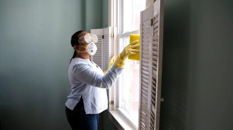 Woman in mask and goggles, cleaning a window