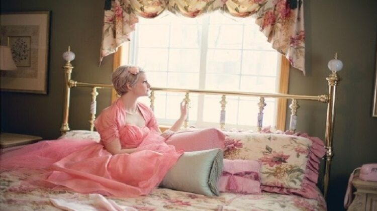 Woman in pink dress on bed with floral Bedspread - Your Bedroom Should Be Brilliant