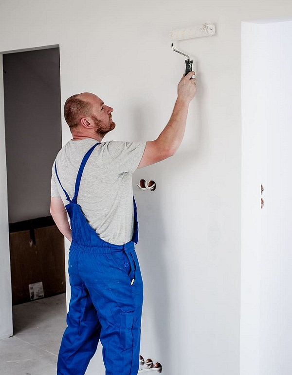 Man in blue coveralls painting a wall - Choose the Right Paint