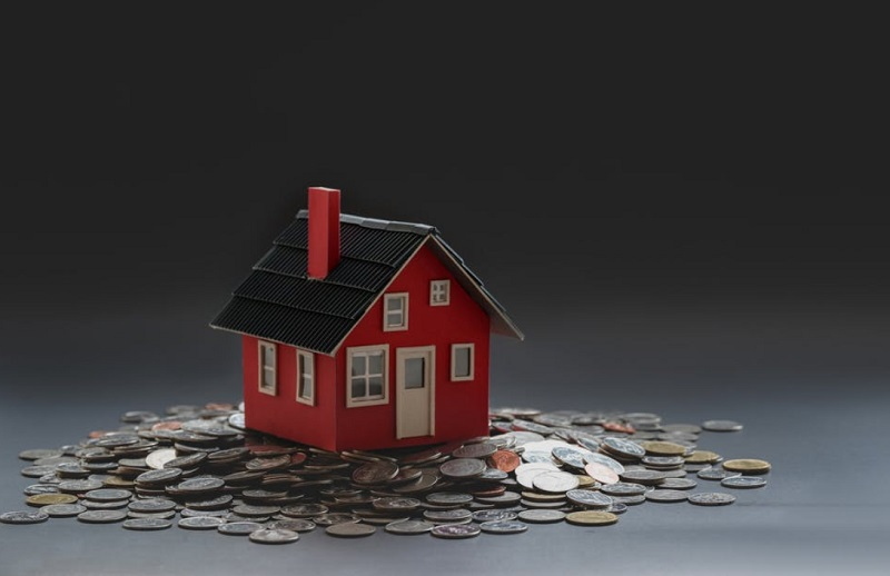 Little Red Toy House sitting on a pile of Coins - Everything You Need To Know About Mortgages