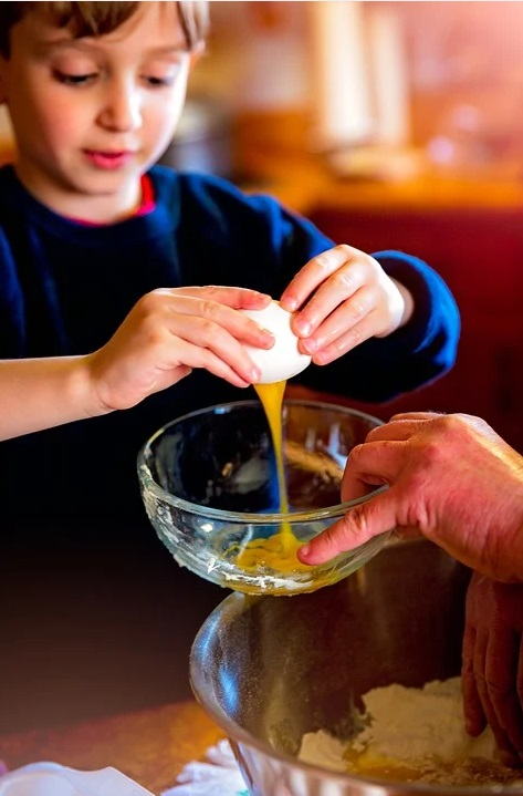 Little boy cracking an egg into a bowl - Fun Activities you Can do on a Rainy Day