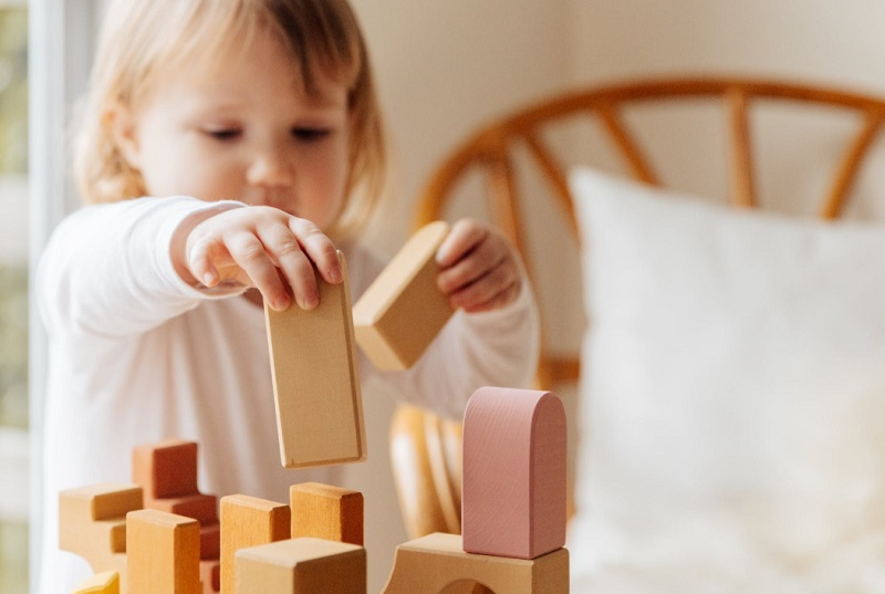 Little girl playing with blocks - Fun Activities you Can do on a Rainy Day