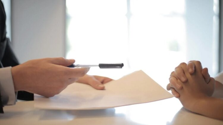 Man holding pen and paper across desk -Everything You Need To Know About Mortgages