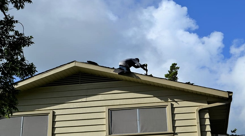Man repairing roof under a blue sky - Roofing Contractor