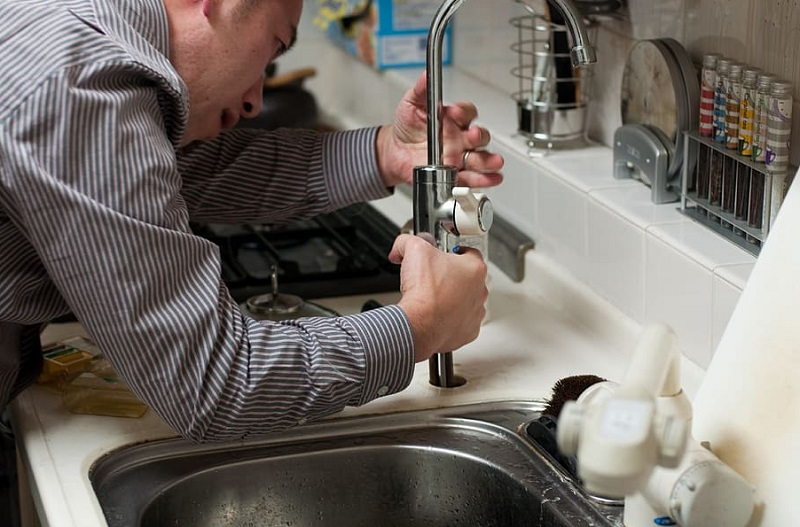 Plumber working on Sink in Kitchen - Plumbing Service For Heater Replacement
