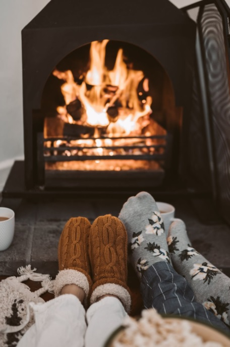 Stockinged Feet in Front of a Fire Burning in a FirePlace