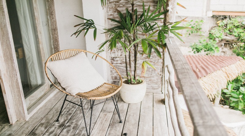 Rattan Chair on Wooden Balcony with Potted Plant A Home That Raises Your Wellness