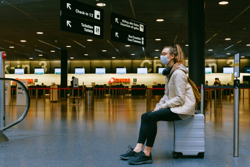 Woman wearing mask seated on luggage in airport Coronavirus and Travel