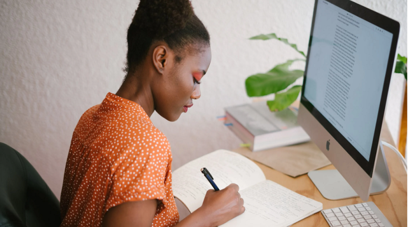 Young woman sitting at desk with computer writing in notebook Online Degree