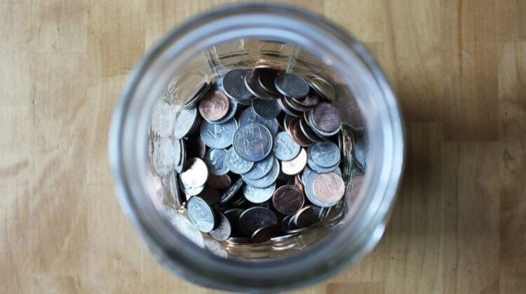 Ways of Saving Money in and Around the Home Jar full of coins on a wood table