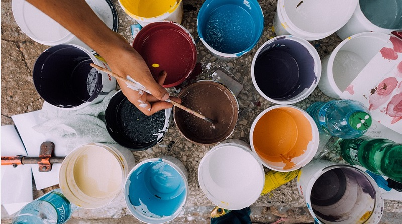 Simple Home Renovations Person dipping paintbrush into open paint can.