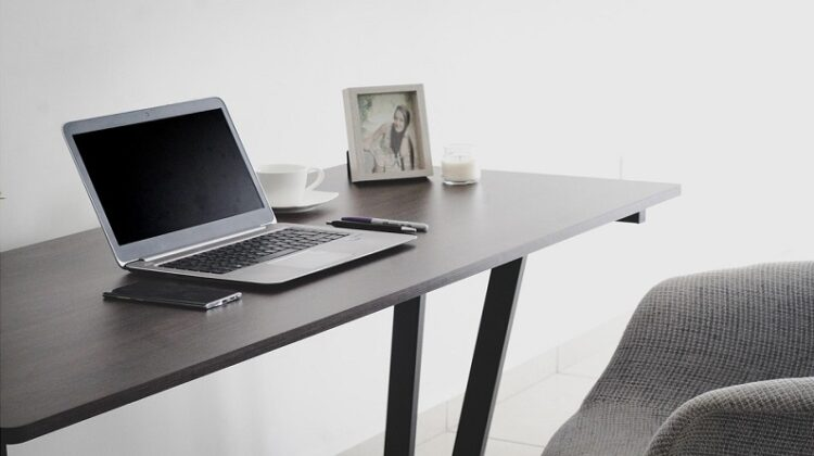 Transforming Your Home Into A Healthy Space Home office with laptop, phone, cup, and photo on simple desk