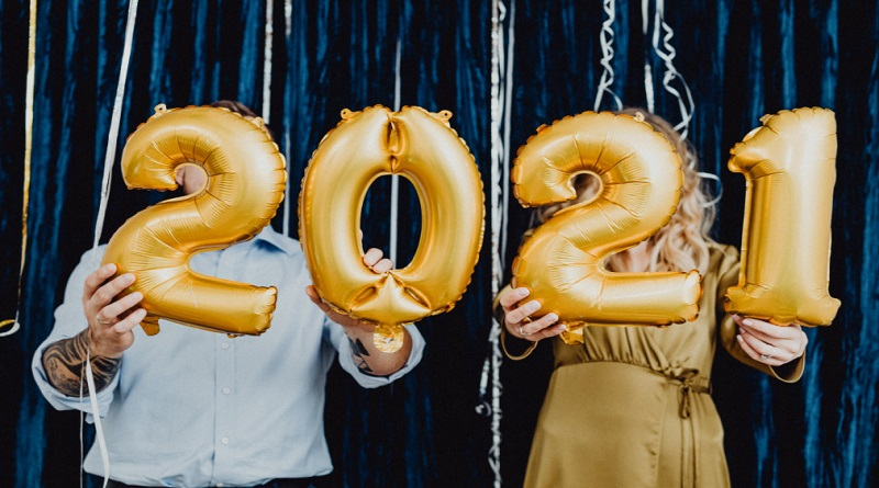 Set a New Year's Resolution Man and woman holding up new years balloons