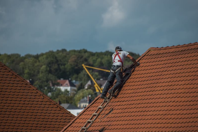 Roofing Services Man in harness working on roof repair