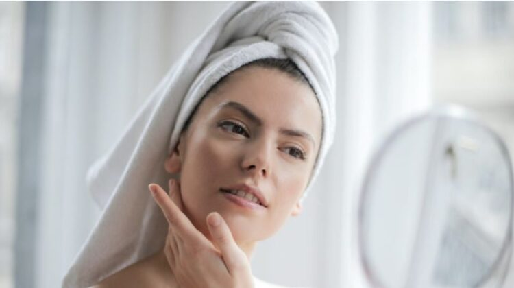 Common Skin Problems Woman wearing no makeup and with her hair wrapped in a towel looking into a mirror