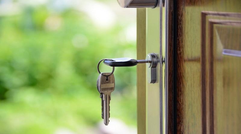 Keys in front door of home