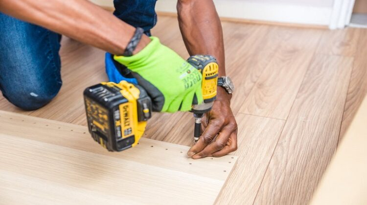 Home Refurbishment Man with drill making holes in a large sheet of wood