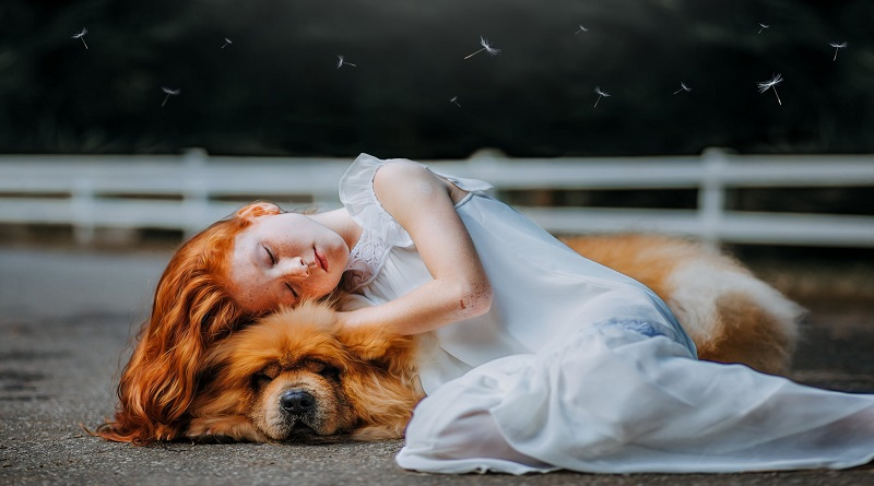 Is Your Child An Introvert Red headed little girl in white gown snuggling with a dog