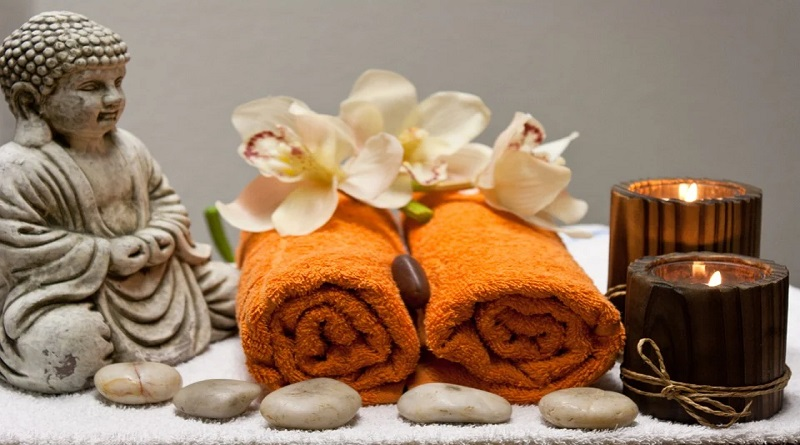A Little Pampering Rolled up towels, lighted candles, flowers, and a Buddha