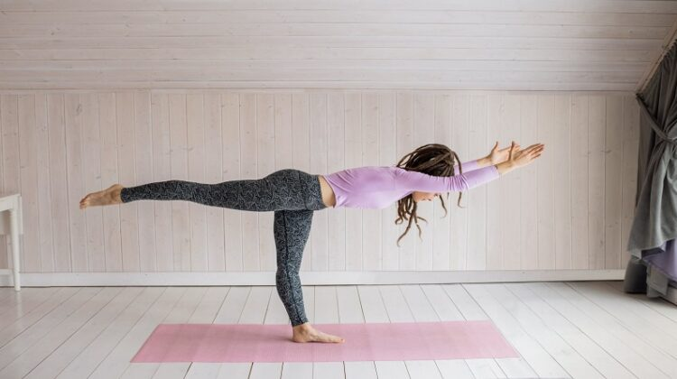 Yoga Woman in grey pants and lilac top doing yoga on pink mat