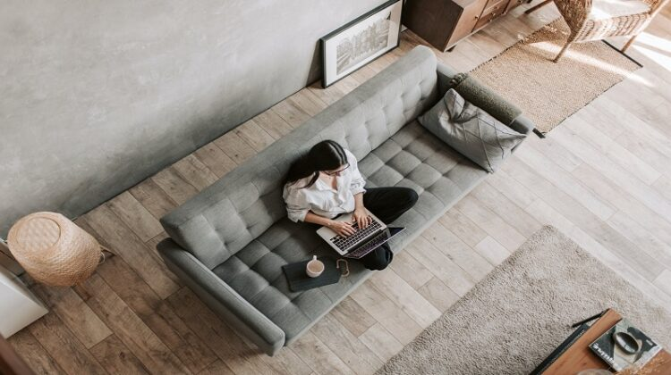 Working Remotely Woman sitting on Grey Sofa working on Laptop