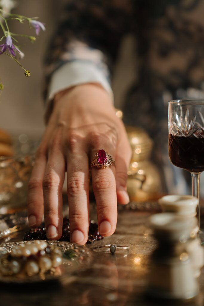 Jewellry Etiquette Hand with ring with red gem in gold setting
