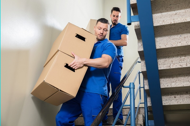 Movers carrying boxes down stairs Benefits of Hiring Removalists