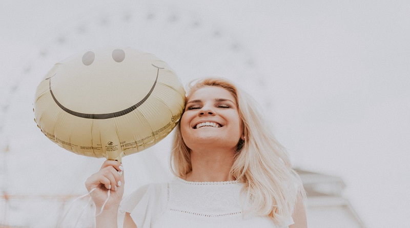 Smiling Blonde Woman Holding a Happy Face Balloon