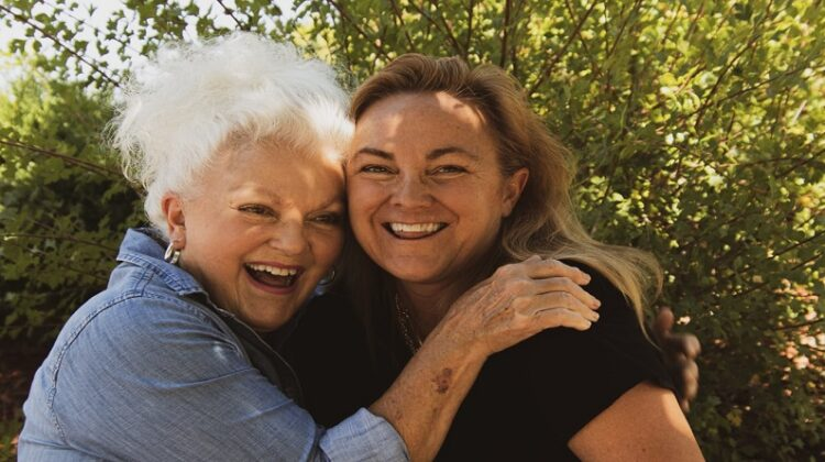 Fighting Age Two mature women hugging and smiling