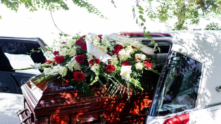To-Do's to Say The Last Goodbye to your Beloved with Love and Care White Hearse with Casket adorned with Red and White Roses