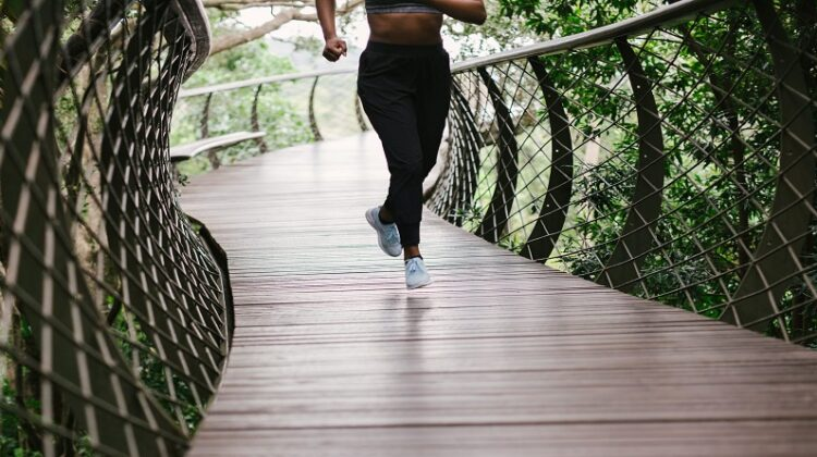 Latest Fitness Trends Woman Running on wooden trail