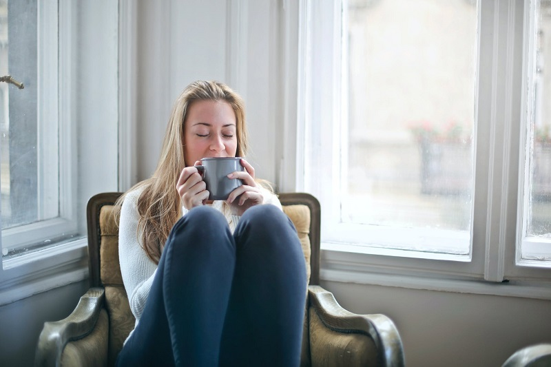 How To Give Your Confidence A Boost Woman in Jeans and White Sweater Sitting in Chair with Knees Up and Holding a Cup