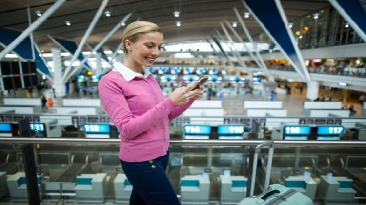 Woman in Pink top and Jeans using smartphone in airport