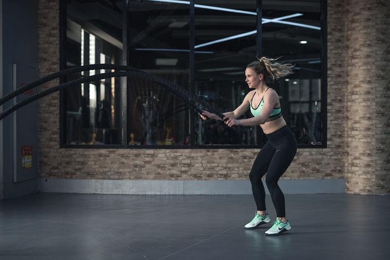 Woman in Workout Clothes at Gym with Huge Jump Ropes